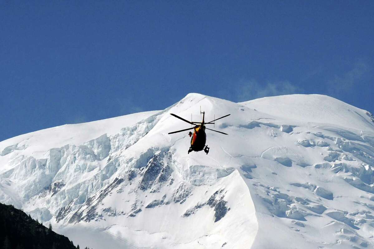A rescue crew of the Securite Civile (emergency services) flies over the Mont Blanc massif in an helicopter on Thursdayin Chamonix, in the French Alps, to the Mont Maudit, a mountain in the Mont Blanc Massif where an avalanche killed at least nine people. Local authorities said the avalanche was