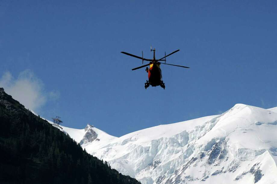 """A rescue crew of the Securite Civile (emergency services) flies over the Mont Blanc massif in an helicopter on Thursday in Chamonix, in the French Alps, to the Mont Maudit, a mountain in the Mont Blanc Massif where an avalanche killed at least nine people.  Local authorities said the avalanche was """"the most deadly of recent years"""".   AFP PHOTO JEAN-PIERRE CLATOT  Photo: JEAN-PIERRE CLATOT, Ap/getty / 2012 AFP"""