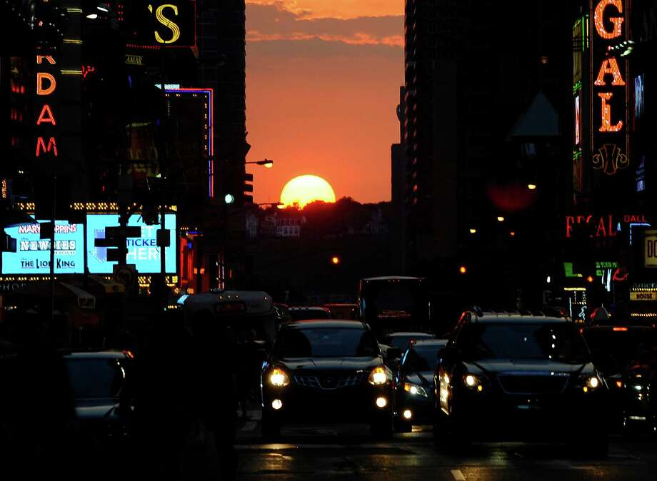 The sun sets as seen from 42nd street in New York City on July 11, 2012,  as Manhattanhenge, sometimes also referred to as Manhattan Solstice, the biannual natural event, when it is perfectly aligned with Manhattan?s numbered streets. AFP PHOTO / TIMOTHY A. CLARYTIMOTHY A. CLARY/AFP/GettyImages Photo: TIMOTHY A. CLARY, AFP/Getty Images / AFP