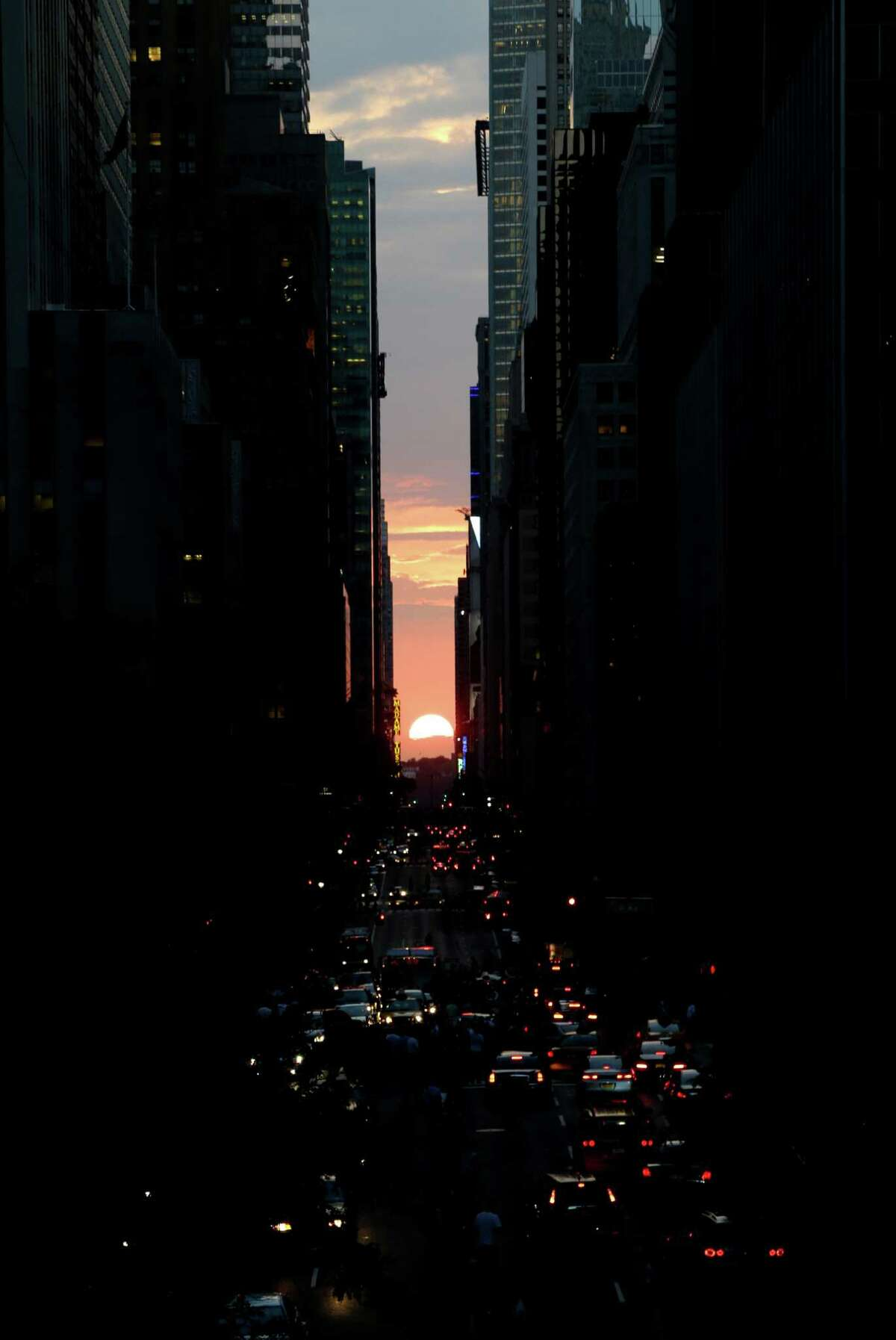 The sun sets through the middle of buildings on 42nd Street in New York's Manhattan borough, during a phenomenon known as Manhattanhenge, Wednesday, July 11, 2012. Manhattanhenge, sometimes referred to as the Manhattan Solstice, happens when the setting sun aligns with the east-to-west streets of the main street grid. The term references Stonehenge, at which the sun aligns with the stones on the solstices in England.