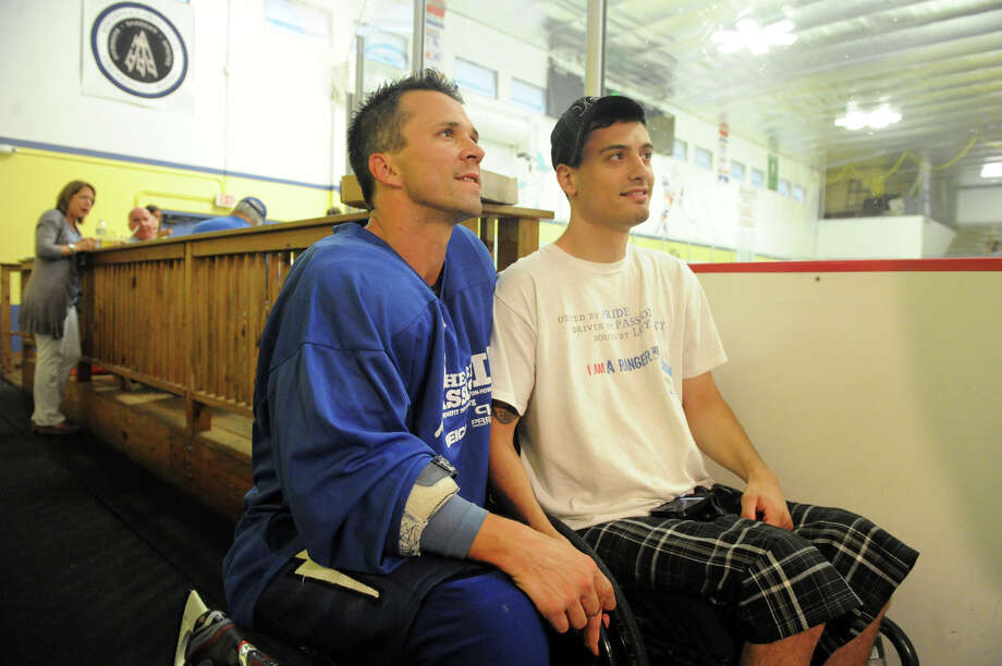 Martin St. Louis poses for a photograph with Stathi Hasiotis during the Big Assist IV ice hockey exhibition game to benefit the Obie Harrington-Howes Foundation at Terry Conners Ice Rink in Stamford, Conn., July 11, 2012. Photo: Keelin Daly / Stamford Advocate
