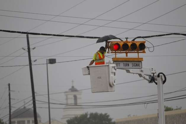 Worker takes on a traffic light during storms and heavy rain in Houston Thursday, July 12, 2012. Photo: Michael Paulsen, Michael Paulsen / Chronicle / Houston Chronicle