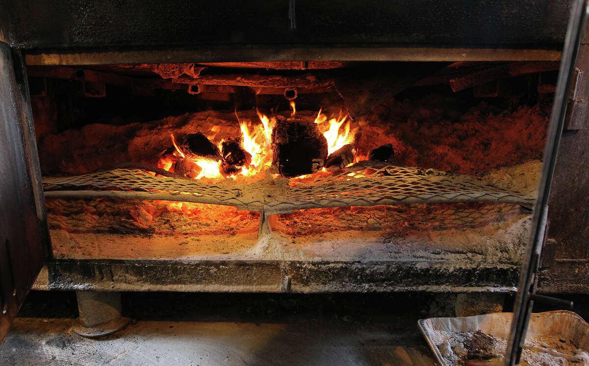 The fire in an enormous smoker fired with Oak wood never goes out except for cleaning at Buzzie's BBQ in Kerrville. Harold