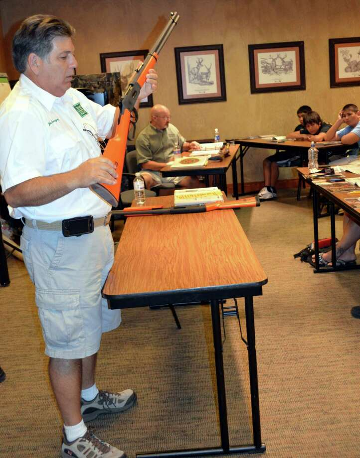 Going over basic safety guidelines with non-firing firearms, John Rodriguez, chief instructor of the San Antonio area, conducts a Hunters Education Training Course at Bass Pro Shops. Photo: Ralph Winningham / For The E-N