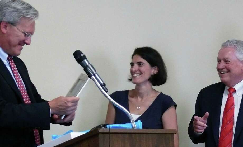 Former Selecmtan James Walsh, left, receives a gift from Selectman Cristin McCarthy Vahey and First Selectman Mike Tetreau. Walsh has been named to the Board of Finance. Photo: Genevieve Reilly / Fairfield Citizen