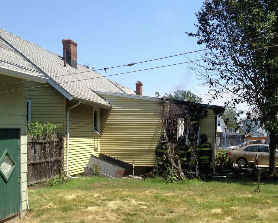 Firefighters vent smoke from a house fire at 17 Harvey St., Bridgeport. July 12,2012 Photo: Frank Juliano