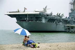 KRT TRAVEL STORY SLUGGED: UST-GULFCOAST KRT PHOTOGRAPH BY ALAN SOLOMON/CHICAGO TRIBUNE (June 23) A woman and child find peace in the shadow of the once-mighty USS Lexington, a World War II aircraft carrier that's now a museum off Corpus Christi Beach in Texas. (mvw) 2003