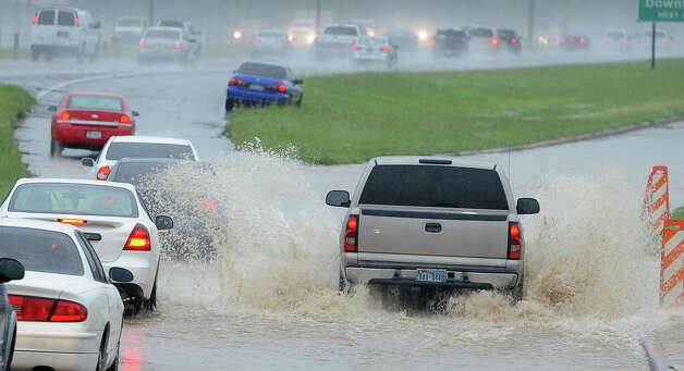 A truck passes several cars that are slowed by flooding along U.S. 69 in Beaumont on Thursday. Heavy rains triggered several accidents, flash flood warnings and complications for Southeast Texas travelers.  Photo taken Thursday, July 12, 2012 Guiseppe Barranco/The Enterprise Photo: Guiseppe Barranco, STAFF PHOTOGRAPHER / The Beaumont Enterprise