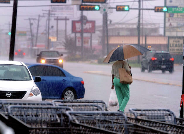 A woman carries groceries across 11th Street in Beaumont on Thursday. Heavy rains triggered several accidents, flash flood warnings and complications for Southeast Texas travelers.  Photo taken Thursday, July 12, 2012 Guiseppe Barranco/The Enterprise Photo: Guiseppe Barranco, STAFF PHOTOGRAPHER / The Beaumont Enterprise