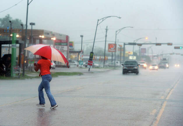 A woman runs across 11th Street in Beaumont on Thursday. Heavy rains triggered several accidents, flash flood warnings and complications for Southeast Texas travelers.  Photo taken Thursday, July 12, 2012 Guiseppe Barranco/The Enterprise Photo: Guiseppe Barranco, STAFF PHOTOGRAPHER / The Beaumont Enterprise