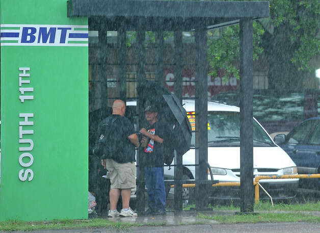 Two men talk while waiting on an 11th Street bus Thursday. Heavy rains triggered several accidents, flash flood warnings and complications for Southeast Texas travelers.  Photo taken Thursday, July 12, 2012 Guiseppe Barranco/The Enterprise Photo: Guiseppe Barranco, STAFF PHOTOGRAPHER / The Beaumont Enterprise