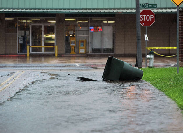 A garbage can floats toward Calder Avenue in Beaumont on Thursday. Heavy rains triggered several accidents, flash flood warnings and complications for Southeast Texas travelers.  Photo taken Thursday, July 12, 2012 Guiseppe Barranco/The Enterprise Photo: Guiseppe Barranco, STAFF PHOTOGRAPHER / The Beaumont Enterprise
