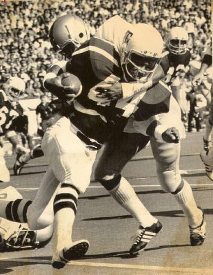 A&M running back Bubba Bean is hauled down while playing against SMU in 1975, wearing a maroon jersey with shoulder stripes, white pants and a white helmet. Adidas said they used this design as a starting point for their redesign.  (  Express-News photo archive)