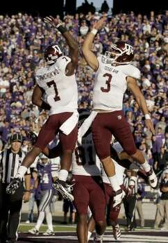 In 2011, the road unis were all white jerseys with all maroon pants. Here, quarterback Jameill Showers (3) and wide receiver Uzoma Nwachukwu (7) celebrate after Showers scored a touchdown at Kansas State on Nov. 12.  (Charlie Riedel / AP)