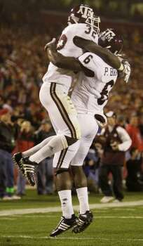 In this 2008 game at Iowa State, the pants were white instead of maroon as Garrick Williams (32) celebrated with teammate Pierre Brown (6) after scoring a touchdown.  (Charlie Neibergall / AP)