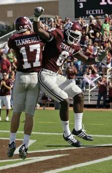 In this 2008 home game against Colorado, Texas A&M's Jeff Fuller (8) celebrated a TD with Ryan Tannehill while sporting grey pants with stripes.  (David J. Phillip / AP)