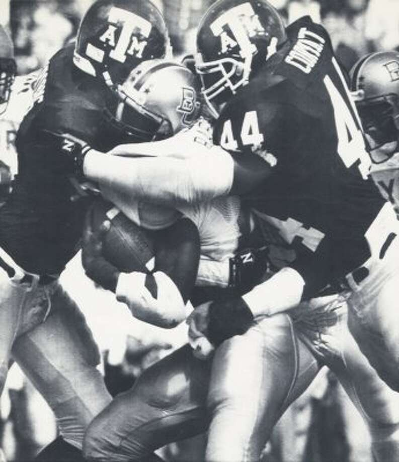 It was the same look the Aggies wore for 1990 home games, like this one when Quentin Coryatt and Chris Crooms tackled a Baylor running back.  (File / Associated Press)