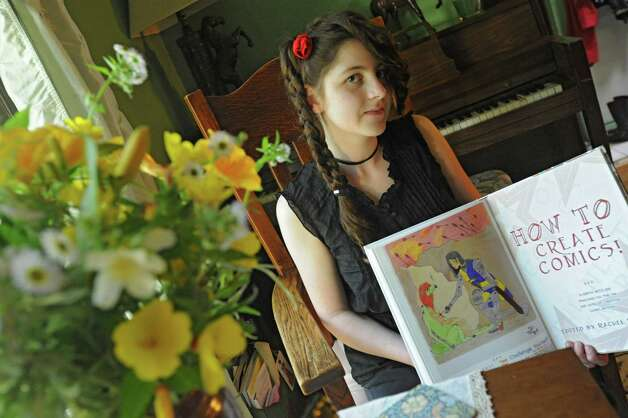 Ceili Conway, a 14 year old who had work published in the Womenthology comic, holds the book open to her page at her home June 11, 2012 in Selkirk, N.Y.  (Lori Van Buren / Times Union) Photo: Lori Van Buren