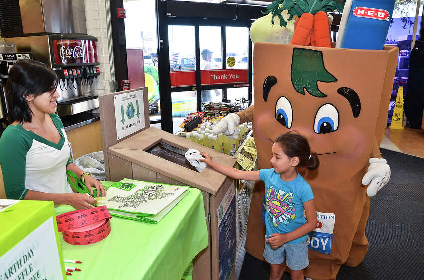 HEB associate Yessie Flores, left, looks on as 5-year-old Rylee Gaona gets directions from H-E-Buddy in recycling plastic bags in exchange for a reusable shopping bag Sunday morning at the HEB Store on Saunders St. HEB was offering the bags in exchange for plastic bags in celebration of Earth Day 2012.