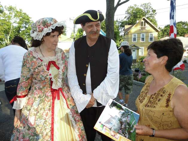 Ed Eckert, vice president of the Norwalk Historical Society, and his wife Madeleine, dressed in period costumes, chat with Maria Cruz during the re-dedication ceremony for the Battle of Flax Hill Monument. Photo: Meg Barone