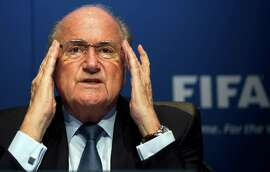"""FILE - In this March 30, 2012 file picture FIFA President Sepp Blatter gestures during a press conference at the FIFA headquarters in Zurich, Switzerland.  FIFA President Sepp Blatter defended his role in a World Cup kickbacks scandal on Thursday July 12, 2012, after his former boss Joao Havelange was formally identified for taking millions of dollars in payments from marketing deals.  FIFA published a Swiss prosecutor's report on Wednesday confirming that Havelange accepted kickbacks in the 1990s during Blatter's 17-year stint serving him as FIFA's top administrator. Asked if he knew that Havelange took kickbacks from disgraced marketing agency ISL, Blatter said """"commission"""" payments were legal in Switzerland in the 1990s."""