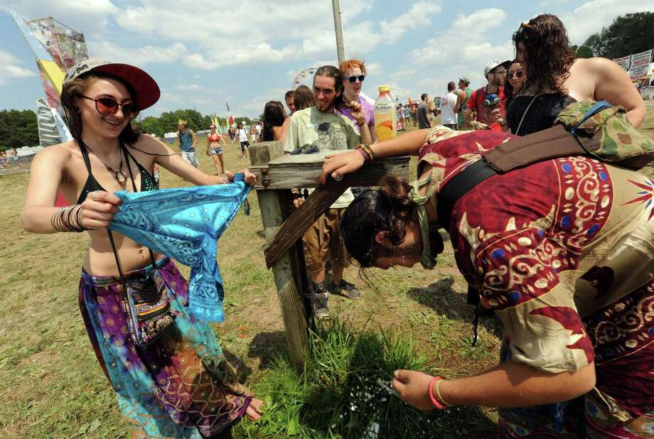 Samanrha Sic, left, and Dan Fran, right, cool off at a water spigot as Camp Bisco 11 kicks off in Pattersonville NY Thurssday  July 12, 2012. (Michael P. Farrell/Times Union) Photo: Michael P. Farrell