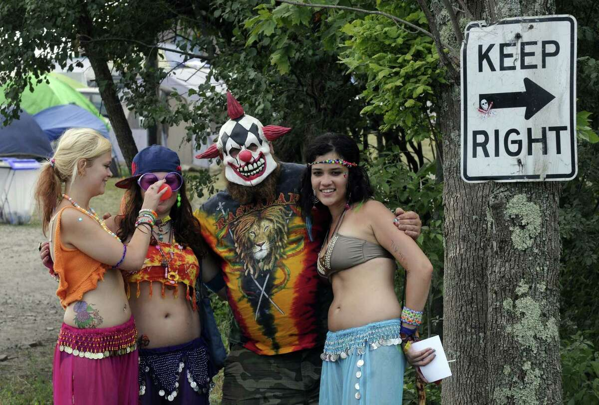 A masked gentaleman named Fro from Schenectady posses with some lady concert goers as Camp Bisco 11 kicks off in Pattersonville NY Thurssday July 12, 2012. (Michael P. Farrell/Times Union)