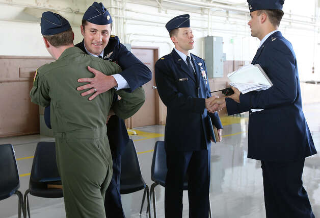 Major Joshua M. Hallada (second from left) receives a hug as he and long-time friend Maj. Philip A. Bryant (second from right) were recipients of Silver Star medals after a ceremony at Randolph Air Force Base on Thursday, July 12, 2012. The two men were honored for their bravery and efforts in extracting two downed U.S. Army pilots as part of the 83rd Expeditionary Rescue Squadron located at Bagram Air Base in Afghanistan in April, 2011. The Silver Star is the third highest award for combat military decoration. The service crosses are ranked second highest and the Medal of Honor is the first highest in awards for the military. Photo: Kin Man Hui, SAN ANTONIO EXPRESS-NEWS / ©2012 SAN ANTONIO EXPRESS-NEWS