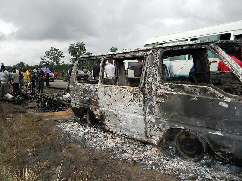 People gather next to a burnt minibus after a Nigerian petrol tanker tipped over and pools of spilled oil caught fire in Okogbe on July 12, 2012. More than 100 people who rushed to scoop up fuel after a Nigerian petrol tanker tipped over on July 12 were killed. Children were among those killed, while dozens more were badly burned, despite a warning from troops who arrived at the crash site that a blaze could ignite at any moment. The tanker driving in the southern Rivers state swerved as it was trying to avoid a collision with three oncoming vehicles including a bus, said Kayode Olagunju, head of the state's Federal Road Safety Commission. AFP PHOTO/STRSTR/AFP/GettyImages Photo: Str, AFP/Getty Images