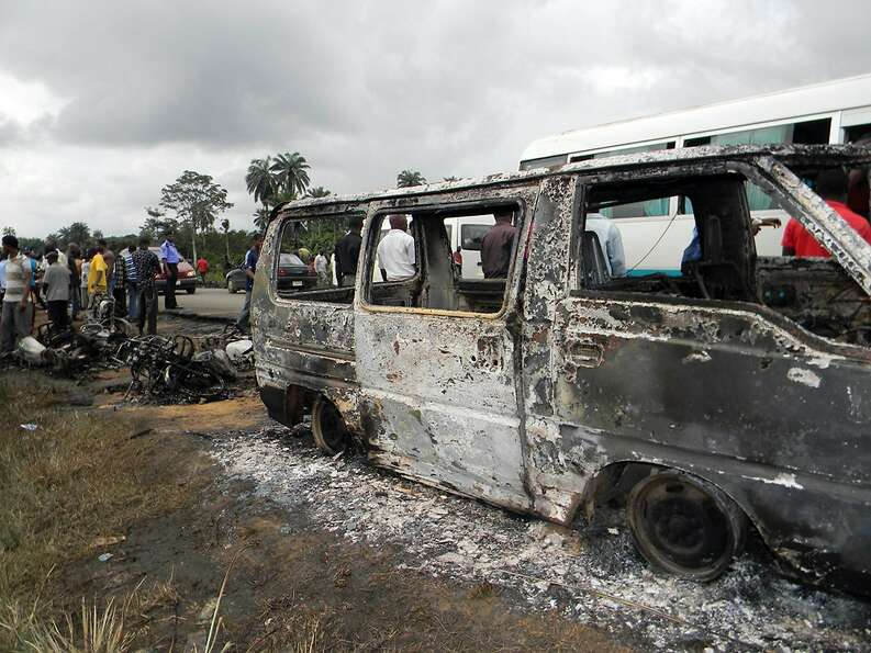 People gather next to a burnt minibus after a Nigerian petrol tanker tipped over and pools of spille