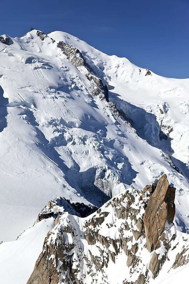 """FILE - In this June 4, 2010 file picture the glaciated northern flank of """"Mont Maudit"""" and """"Mont Blanc"""" on 4808 meters above sea level, far back, """"Bosses"""" ridge and the """"Col du Dome"""" peak, right, as well as """"Arete des Cosmiques"""" with the """"Cosmiques"""" alpine hut, in the foreground below, is photographed above Chamonix, France. An avalanche in the French Alps on Thursday July 12, 2012 swept six climbers from several European countries to their deaths on a slope leading to Mont Blanc, left at least nine injured and several others unaccounted for, authorities said. Rescuers are searching for the missing. (AP Photo/Keystone/Arno Balzarini) Photo: Arno Balzarini, Associated Press"""