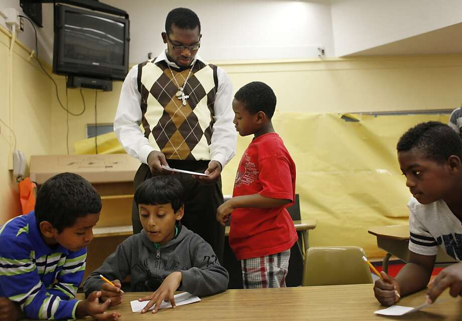 Mentor Thomas Morris (back left), Rose-Hulman Institute of Technology software engineer major helps Jonathan Lacey (back right), 9 with his worksheet to identify the parts of a machine as Mohammed Dharhan (foreground l to r) , 7; Adam Saleh, 7 and Clinton Johnson, 8 work on their worksheets during the Summer Engineering Experience for Kids program at the Martin Luther King Jr. Elementary School on Tuesday, July 10, 2012 in Oakland, Calif. Photo: Lea Suzuki, The Chronicle