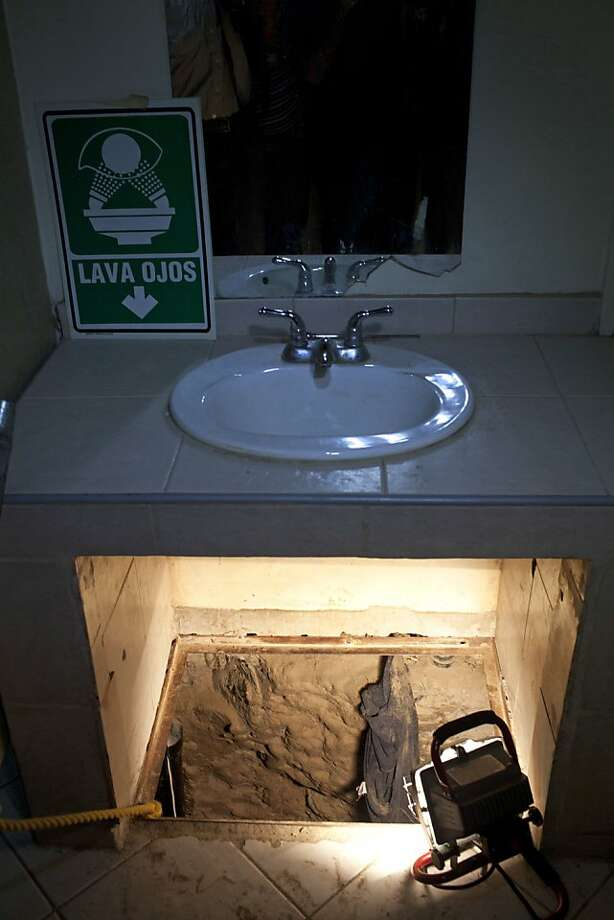 The entrance to a cross border illegal tunnel is lit by a lamp after it was found underneath a bathroom sink by the Mexican army inside a warehouse in Tijuana, Mexico, Thursday July 12, 2012. The 220-yard  tunnel, presumably designed to smuggle drugs into the United States, was incomplete and had not yet crossed the border into San Diego. (AP Photo/Alejandro Cossio) Photo: Alejandro Cossio, Associated Press