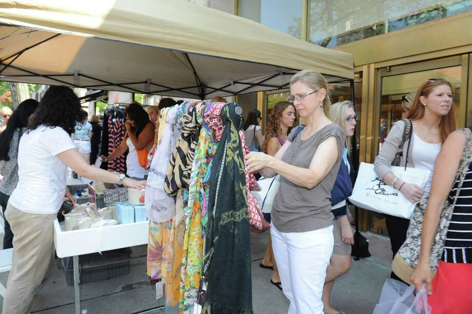 Ruth Milano, of New Canaan, looks at scarves at Saks Fifth Avenue at the Greenwich Sidewalk Sale Days Thursday, July 12, 2012. The Greenwich Chamber of Commerce presents the 2012 Greenwich Sidewalk Sales from 10 a.m. to 6 p.m. July 12-15. Shops and boutiques on Greenwich Avenue and surrounding streets will offer sales and discounted prices on a wide variety of merchandise over the course of these four days. The weekend will also feature song and dance performances and children's entertainment. Photo: Helen Neafsey / Greenwich Time
