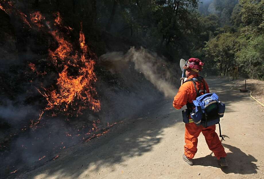 An inmate from the Eel River Conservation camp throws dirt on flames  from the Robbers fire near Iowa Hill, Calif., Thursday, July 12, 2012.  The fire that broke out Wednesday afternoon has consumed more than 500 acres and forced the evacuation of about 40 people.  No homes have been destroyed as more than 300 firefighters aided by air tankers and helicopters battle the flames. (AP Photo/Rich Pedroncelli) Photo: Rich Pedroncelli, Associated Press