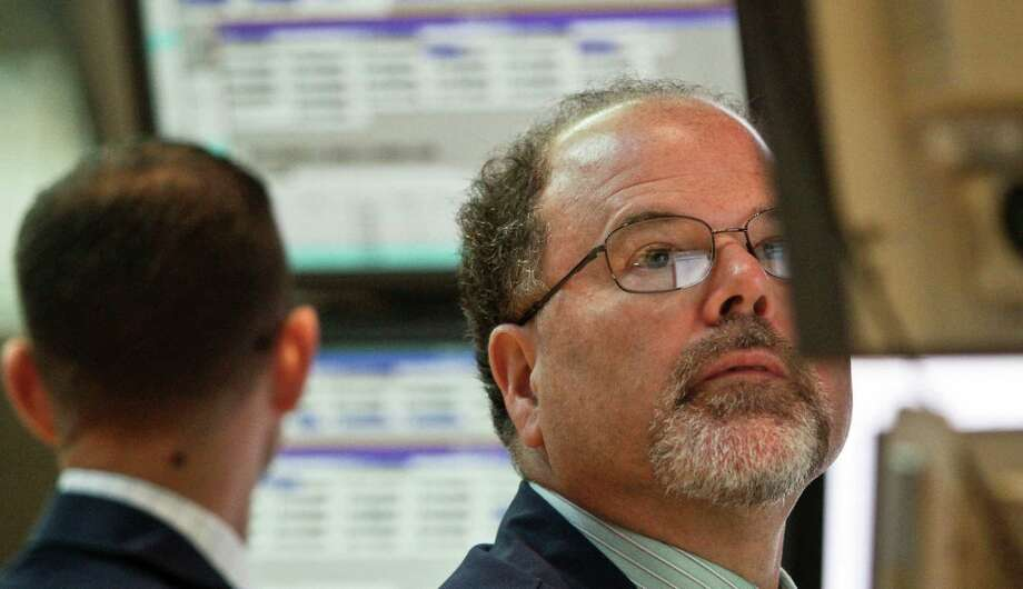 FILE- In this Tuesday, July 10, 2012, file photo, Douglas Johnson, a trader for Getco Securities from Levittown, Pa., works during early trading at the New York Stock Exchange. U.S. share futures also pointed down Thursday July 12, 2012 ahead of the New York open. The Dow industrials index was off 0.34 percent in pre-market trading at 12,493.00 and the Standard & Poors 500 fell 0.55 to 1,328.90. ( AP Photo/Bebeto Matthews, File) Photo: Bebeto Matthews