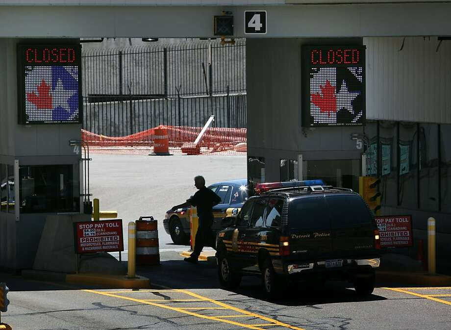 Police vehicles stand at toll booths on the Detroit side of the temporarily closed Detroit Windsor Tunnel on Thursday, July 12, 2012. The international commuter tunnel connecting Detroit to Windsor, Ontario, was closed for nearly four hours after a bomb threat was phoned in on the Canadian side. No explosives were found. (AP Photo/Detroit Free Press, Susan Tusa) DETROIT NEWS OUT  TV OUT  MAGS OUT  NO SALES  MANDATORY CREDIT Photo: Susan Tusa, Associated Press