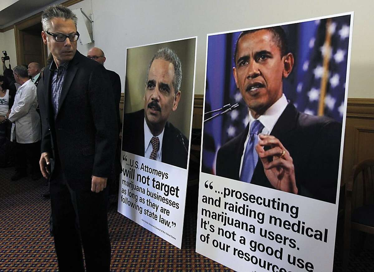Andrew DeAngelo, co-founder of the Harborside Health Center, glances at photos and quotes from U.S. Attorney General Eric Holder and President Obama at a news conference after the federal government threatened to seize assets and shut down the medical marijuana dispensary in Oakland, Calif. on Thursday, July 12, 2012.