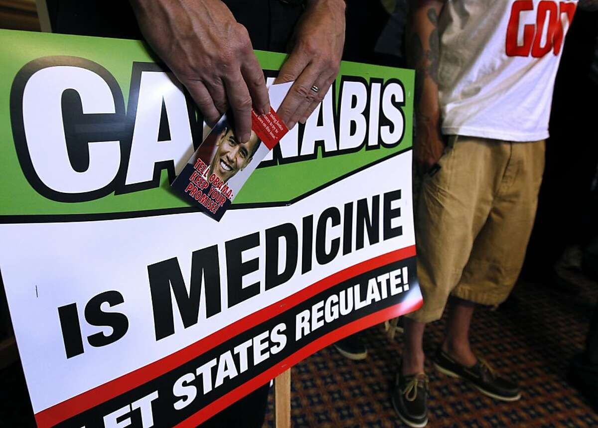 Dale Gieringer, director of California NORML, holds signs at a news conference called to criticize the federal government's threatened plan to seize assets and shut down the Harborside Health Center medical marijuana dispensary in Oakland, Calif. on Thursday, July 12, 2012.