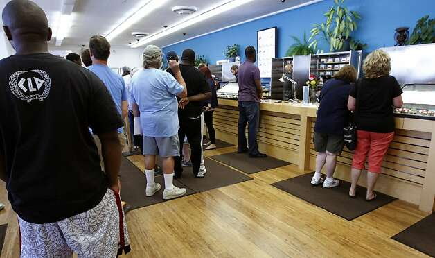 Patients wait in a long line to purchase medical marijuana at the Harborside Health Center in Oakland, Calif. on Thursday, July 12, 2012. The Department of Justice served notice that it plans to seize the assets and shut down Harborside within 20 days. Photo: Paul Chinn, The Chronicle
