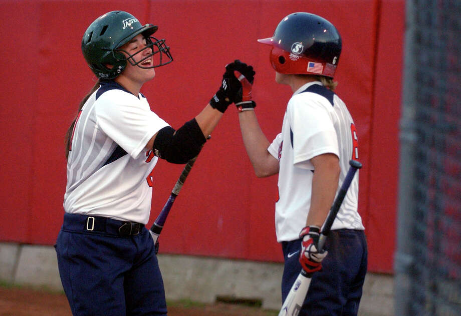 Brakette's #27 Kate Bowen, left, gets a high five from teammate #6 Denise Denis after bringing in a run, during softball action against Newtown Rock in Stratford, Conn. on Thursday July 12, 2012. Photo: Christian Abraham / Connecticut Post