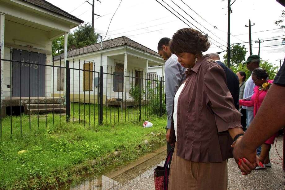 Leu A. Williams bows her head in prayer at the site of row houses following a news conference calling to save the homes Thursday, July 12, 2012, in Houston. Rep. Sheila Jackson Lee and delegates from the NAACP convention visited the site of the shotgun houses, calling for the preservation of the historic homes, and to keep them on this site, in historic Freedmen's Town. Photo: Brett Coomer, Houston Chronicle / © 2012 Houston Chronicle