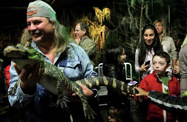 "Bruce Mitchell, star of the History channel's Swamp People, hold a 2-year old swamp alligator as second graders from Manhattan's P.S. 150 clamor for a touch, during a ceremony launching the replica scene of a Louisiana swamp at Chelsea Market on Thursday, Feb. 2, 2012 in New York. The recreation called ""Swamp in the City,"" featuring live alligators, turtles and Cajun music, is a partnership of the History Channel and Louisiana Tourism to raise awareness of the ""culture, music and excitement of Louisiana."" It opens daily through Sunday, Feb. 12. (AP Photo/Bebeto Matthews) Photo: AP, STF / AP2012"