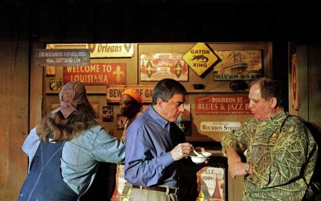 "Louisiana Lieutenant Governor Jay Dardenne, center, samples Cajun cooking from Cajun chef John Folse, right, at the launch of ""Swamp in the City,"" a replica Louisiana swamp and local scene at Chelsea Market on Thursday, Feb. 2, 2012 in New York. The recreation features live alligators, turtles and Cajun music, through a partnership of the History Channel and Louisiana Tourism to raise awareness of the ""culture, music and excitement of Louisiana."" (AP Photo/Bebeto Matthews) Photo: AP, STF / AP2012"