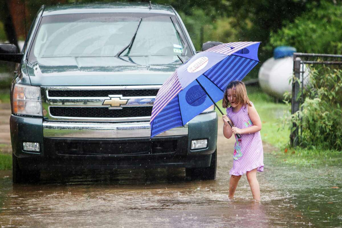 Taylor Kelso, 6, plays in her family's front drive during a rainy downpour that inundated northwest Houston, Thursday, July 12, 2012, in Houston. Kelso and her family received over 5-inches of rain before noon. ( Michael Paulsen / Houston Chronicle )
