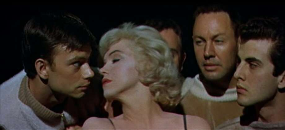 """Let's Make Love"":  Let's give you this kiss in three parts.  Marilyn Monroe has just finished a dance number and decides to be naughty by kissing one of the chorus boys."