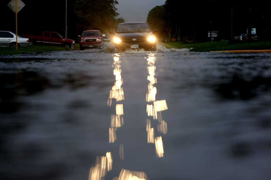 Vehicles drive through slow-receding floodwaters Friday morning near  Huffmeister and Bergenia in the Cypress area. The water was a result of  heavy rains Thursday. Photo: Johnny Hanson, Houston Chronicle