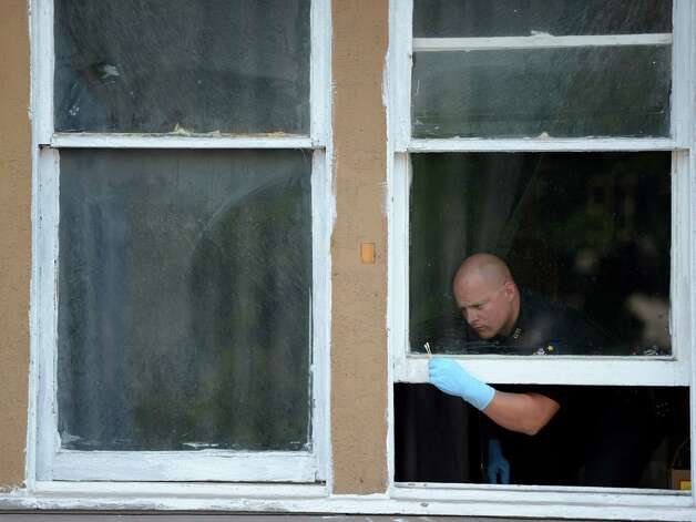 A Troy Police Forensics investigator swabs the window frames of 3022 7th Avenue in Troy, N.Y. after a shooting victim was found inside the building July 13, 2012.   (Skip Dickstein / Times Union) Photo: SKIP DICKSTEIN