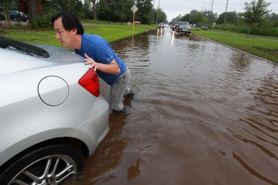 Lam Chau pushes his wife's car Friday morning after it stalled in floodwater near Huffmeister and Bergenia in the Cypress area. The flooding was a result of heavy rains Thursday. Photo: Johnny Hanson, Houston Chronicle