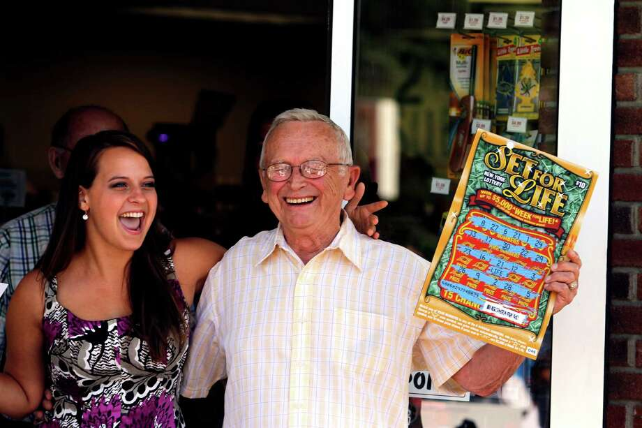 Lottery winner, 80-year-old Stanley Muraski, right, and Gretchen Dizer, left, of the New York State Lottery draw team, step outside of the Stewart's shop where he bought his winning ticket in Waterford, N.Y., Thursday July 12, 2012.  Muraski won the top prize on the Set For Life scratch-off game guaranteeing him at least $5,000,000. (Dan Little/Special to the Times Union) Photo: Dan Little / 00018424A